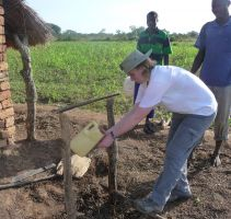 Fiona helping to build a 'tippy tap' in Bobol village, to avoid the spread of disease